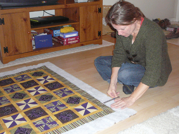 Me pinning the top of the quilt to the batting.